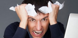 Closeup of a young angry business man having a stress. Headache. Against gray background